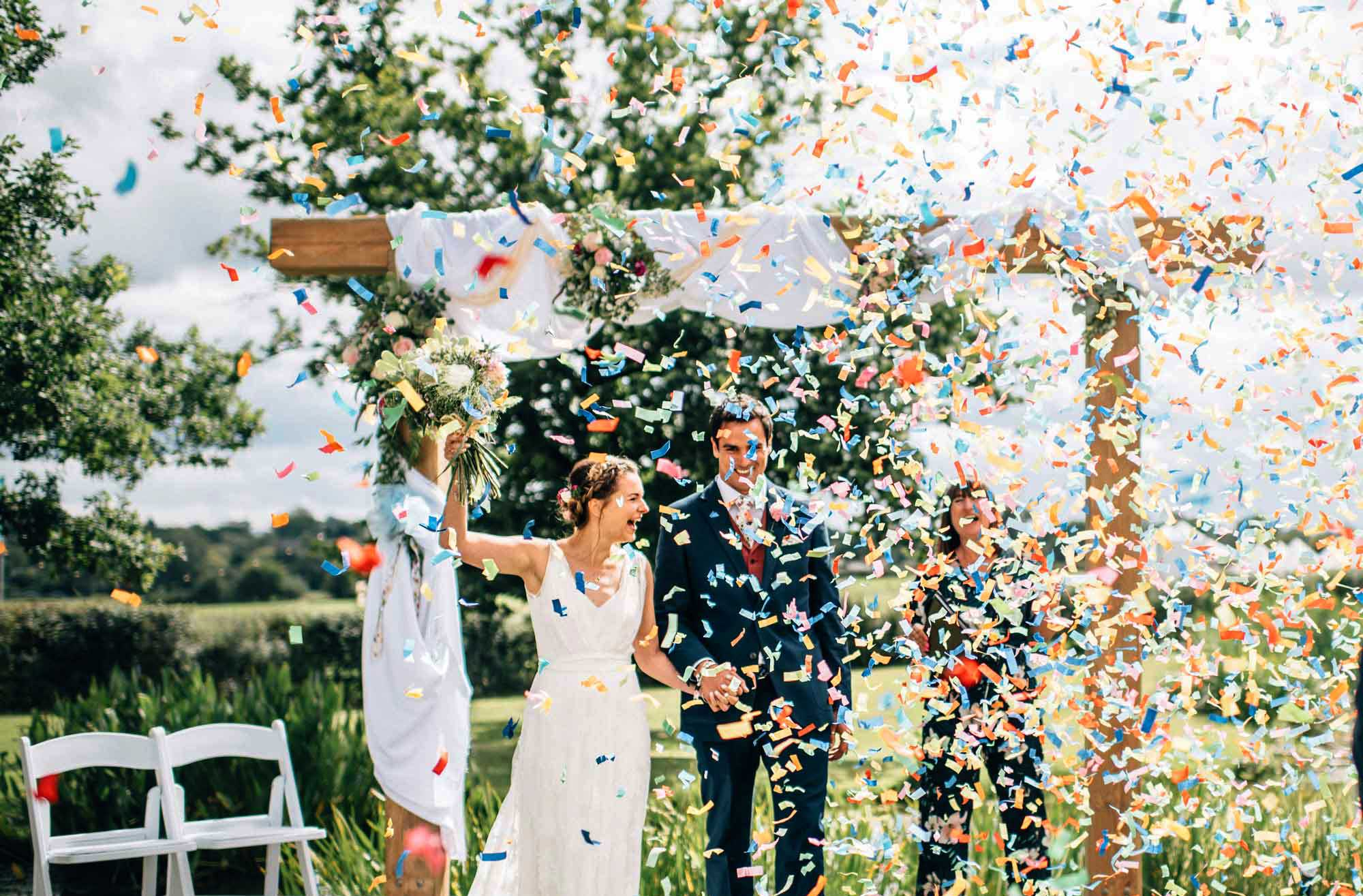 Ella and Rory celebrating their humanist wedding in the countryside with confetti